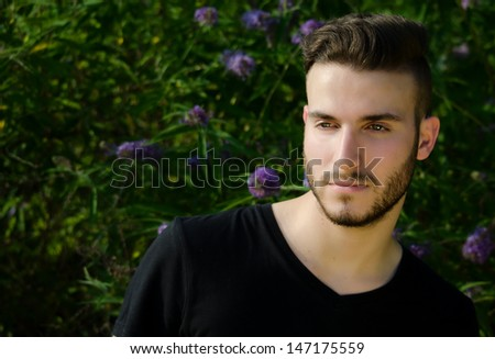 Attractive young man outside, with black t-shirt, serious expression looking off camera, large copyspace - stock photo