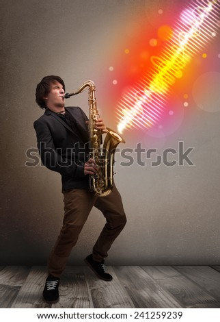 Attractive young man playing on saxophone with colorful sound waves - stock photo