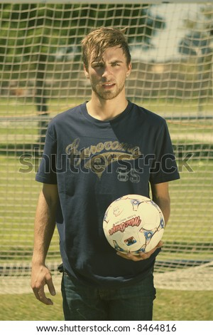 attractive young man playing soccer - stock photo