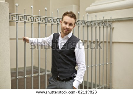 Attractive young man poses opposite a metal fence. - stock photo