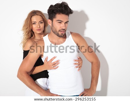 Attractive young man posing in front of his lover while she is embracing him. - stock photo