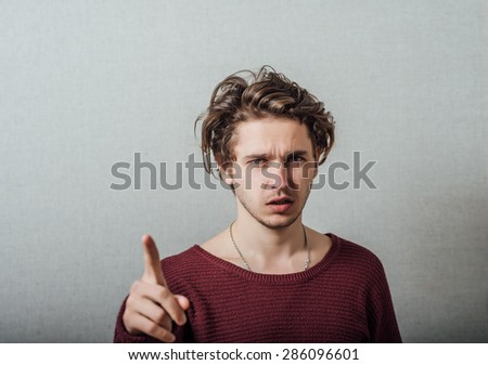 Attractive young man pressing imaginary button in the air with his finger. - stock photo