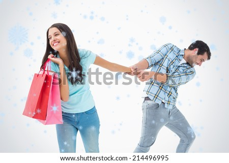 Attractive young man pulling his shopaholic girlfriend against snow falling - stock photo