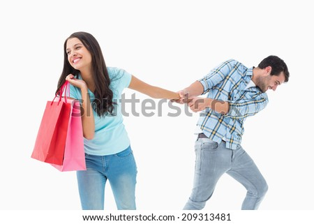 Attractive young man pulling his shopaholic girlfriend on white background - stock photo