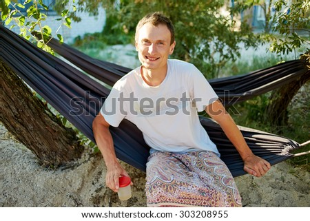 Attractive young man relaxing on a hammock