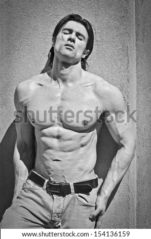 Attractive young man shirtless with jeans leaning against a wall with his eyes closed, black and white shot - stock photo
