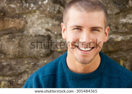 Attractive young man sitting outside. He is smiling at the camera. - stock photo