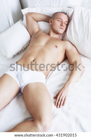 attractive young man sleeping in bed at home - stock photo