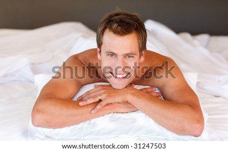 Attractive young man smiling on bed - stock photo