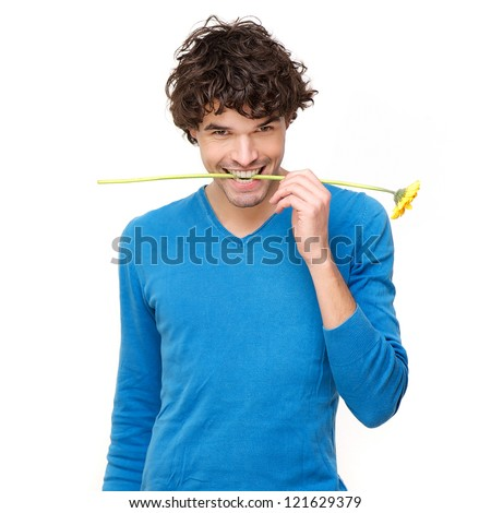 Attractive young man smiling with a yellow flower in his mouth. Isolated on white background - stock photo