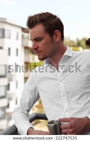 Attractive young man standing on a balcony holding a coffee mug. Wearing a white shirt. - stock photo