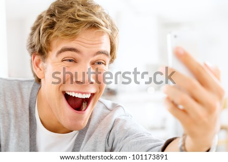 Attractive young man taking self portrait using mobile phone is a