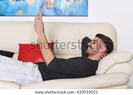 Attractive young man taking selfie with smartphone on white sofa. Indoor.