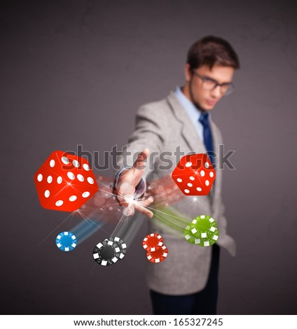 Attractive young man throwing dices and chips - stock photo
