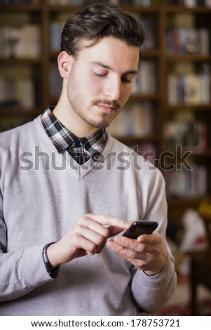 Attractive young man typing on cell phone, indoor shot in house living room - stock photo