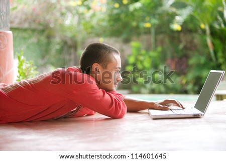 Attractive young man using a laptop computer while laying down in a tropical hotel garden. - stock photo