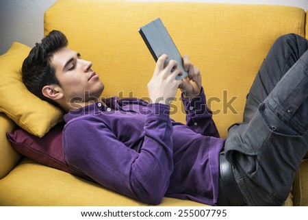 Attractive young man using tablet PC while laying on couch, with serious expression - stock photo