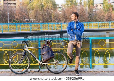 Attractive young man waiting for a friend in a park leaning against colorful railings with folded arms and his bicycle beside him - stock photo