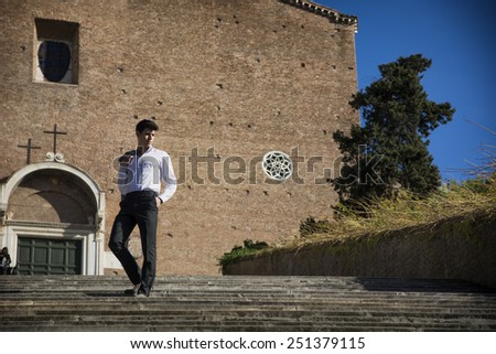 Attractive young man walking down old stair in front of church in Rome, Italy. Large copyspace next to him - stock photo
