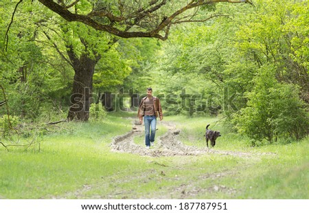 Attractive young man walking in forest with dog - stock photo