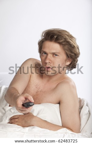 Attractive young man watching adult movies on tv. Studio shot. See more in my portfolio - stock photo