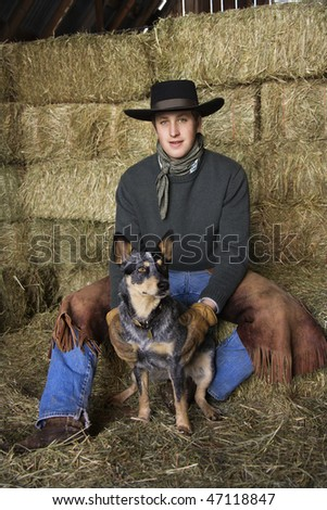 Attractive young man wearing a black cowboy hat, sitting atop a hay bale. He is smiling and holding an Australian Shepherd. Vertical shot. - stock photo
