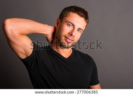 Attractive young man wearing a black t-shirt - stock photo