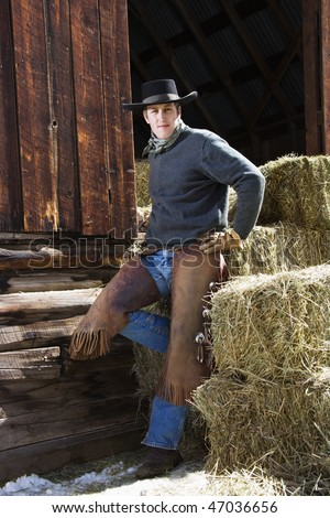 Attractive young man wearing a cowboy hat and chaps. He is leaning on hay bales outside of a barn. Vertical shot. - stock photo