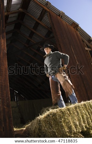 Attractive young man wearing a cowboy hat while standing confidently on top of hay bales. Vertical shot. - stock photo