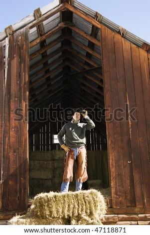 Attractive young man wearing a cowboy hat while standing on top of hay bales. He is tipping up his hat. Vertical shot. - stock photo