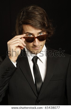 attractive young man wearing elegant black suit and sunglasses - stock photo