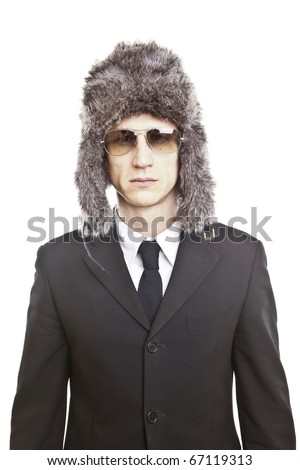 attractive young man wearing elegant black suit,sunglasses and russian hat - stock photo