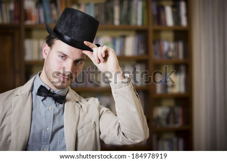 Attractive young man wearing top hat and bow tie, looking at camera. Indoors shot - stock photo