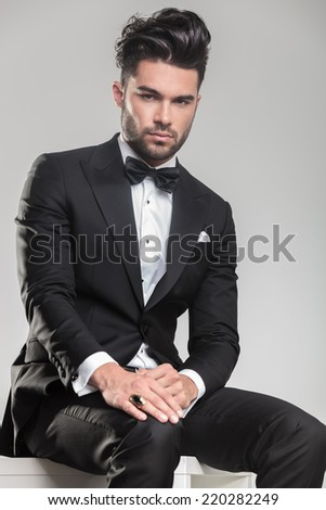 Attractive young man wearing tuxedo sitting and holding one hand onhis knee, looking at the camera.