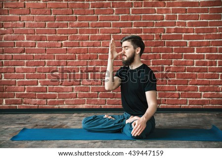 Attractive young man with a beard wearing black T-shirt doing yoga position on blue matt at wall background, copy space, portrait, pranayama exercises. - stock photo