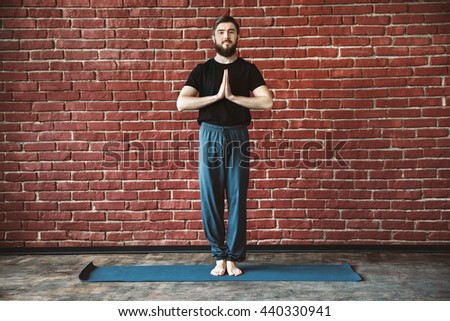 Attractive young man with a beard wearing black T-shirt doing yoga position on blue matt at wall background, copy space, portrait, namaste asana. - stock photo