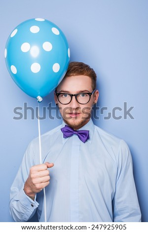 Attractive young man with a blue balloon in his hand. Party, birthday, Valentine. Studio portrait over blue background  - stock photo