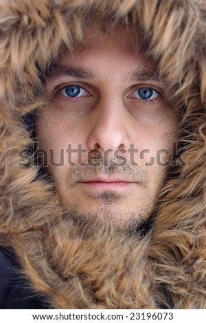 Attractive young man with a blue eyes and hood on his head. - stock photo