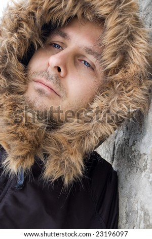 Attractive young man with a blue eyes and hood on his head leaning against the wall. - stock photo