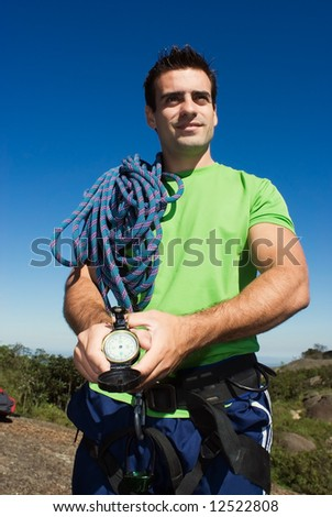 Attractive, young man with a climbing rope and compass on a camping trip - stock photo