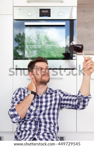 Attractive young man with a glass of wine in a modern kitchen. Young man sitting leaning against the kitchen waiting for his girlfriend. - stock photo