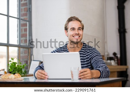 Attractive young man with a gorgeous happy smile sitting working at his laptop at home in his kitchen - stock photo