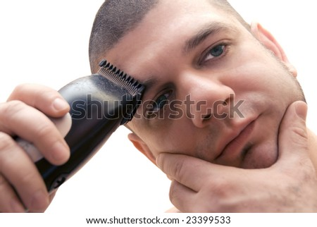 Attractive young man with a green eyes doing hair and eyebrows cut by himself isolated on white background - stock photo