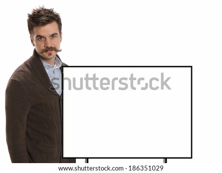Attractive young man with a handlebar mustache and a brown sweater stands in front of a blank white sign with black border, isolated on white - stock photo
