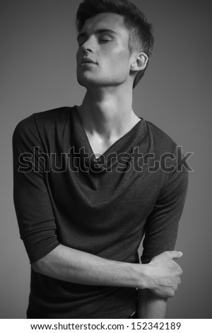 Attractive young man  with beautiful face and his crossed hands, dressed in dark pullover. - stock photo