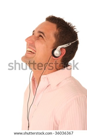 Attractive young man with big smile enjoying listening to music with earphones