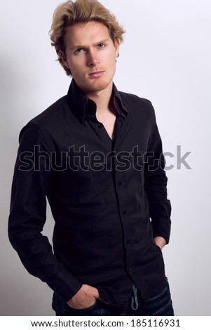 Attractive young man with blonde hair, dressed in black shirt and blue jeans, with hands in his pockets, looking at camera - stock photo