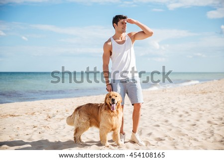 Attractive young man with his dog standing and looking far away on the beach - stock photo
