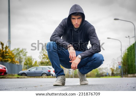 Attractive young man with hoodie and baseball cap in city street, looking at camera - stock photo
