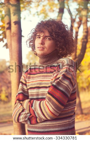 Attractive young man with long curly hair, dressed in striped sweater standing with his arms crossed in autumn park. - stock photo
